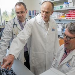 LSARP Collaborators; Drs. Brett Finlay, Mike Kobor and Stuart Turvey analyzing data, 2018; Photo courtesy of Genome Canada; Credit: Canadian Press